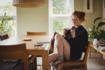 Mujer hermosa mirando fotos en cámara digital en casa - foto de stock