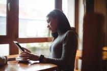 Mulher usando tablet digital enquanto toma uma xícara de café no café — Fotografia de Stock