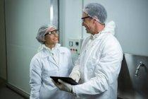 Hombre y mujer discutiendo sobre tableta digital en la fábrica - foto de stock