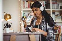 Femme écoutant de la musique sur tablette numérique tout en prenant un café dans le salon à la maison — Photo de stock