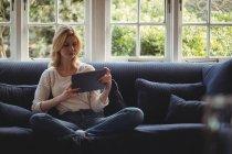Женщина сидит дома на диване с цифровым столом в гостиной — стоковое фото