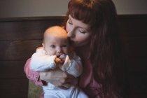 Mère embrasser bébé sur la tête dans le café — Photo de stock