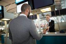 Авіакомпанія-Реєстрація attendant надавши паспорт для пасажирських перевезень на лічильник у терміналі аеропорту — стокове фото