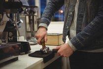 Mann presst Kaffee mit Stampfer in Portafilter in Café — Stockfoto