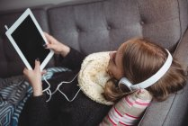 Femme couchée sur le canapé écoutant de la musique sur tablette numérique à la maison — Photo de stock
