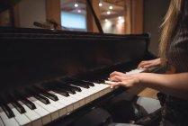 Розділ середині жінка грає на фортепіано в музичну студію — стокове фото