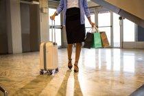 Mujer de negocios caminando con equipaje y bolsas de compras en la terminal del aeropuerto - foto de stock