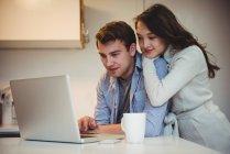 Couple utilisant un ordinateur portable tout en prenant un café dans la cuisine à la maison — Photo de stock