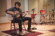 Человек сидит на стуле и играет на гитаре в музыкальной студии — стоковое фото