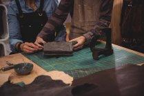 Meados de seção de artesãos discutindo sobre saco de couro na oficina — Fotografia de Stock