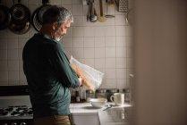 Hombre vertiendo cereales en un tazón en casa - foto de stock