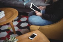 Sezione centrale della donna che utilizza tablet digitale in soggiorno a casa — Foto stock