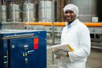 Улыбающийся мужчина с планшетом, стоящий у машины на соковом заводе — стоковое фото