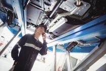 Mechanikerin telefoniert unter Auto in Werkstatt — Stockfoto