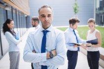 Porträt eines selbstbewussten Geschäftsmannes mit verschränkten Armen, der vor einem Bürogebäude steht — Stockfoto