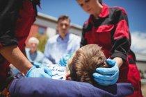 Парамедики осматривают раненого мальчика на улице — стоковое фото