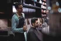 Парикмахер показывает мужчину стриженого в зеркале в парикмахерской — стоковое фото