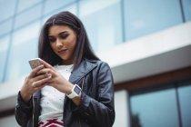 Femme utilisant un téléphone portable à l'extérieur de l'immeuble de bureaux — Photo de stock