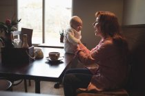 Happy mother playing with baby in cafe interior — Stock Photo