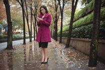 Empresária usando telefone de pé no caminho — Fotografia de Stock