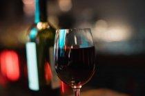 Primer plano del vidrio de vino rojo en la barra de bar en bar - foto de stock