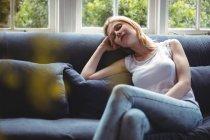 Женщина отдыхает на диване в гостиной дома — стоковое фото