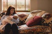 Матери кормящей младенца ребенка на диване в гостиной — стоковое фото