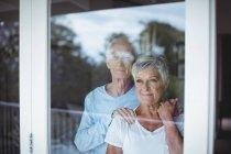 Casal sênior olhando pela janela em casa — Fotografia de Stock