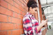 Vista lateral da mulher usando telefone enquanto se inclina na parede de tijolo — Fotografia de Stock