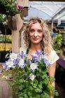Portrait de femme fleuriste tenant en pot plantes en jardinerie — Photo de stock