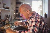 Orfèvre attentif utilisant une machine à pièce à main en atelier — Photo de stock