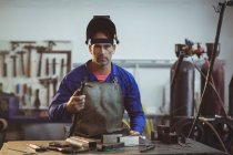 Male welder holding welding torch in workshop — Stock Photo