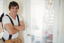 Happy Carpenter standing near repaired door at home — Stock Photo