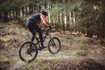 Верховая езда на горном велосипеде по грунтовой дороге в лесах — стоковое фото