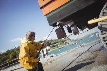 Мужчина чистит лодку посудомоечной машиной в солнечный день — стоковое фото