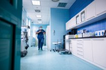 Male surgeon rushing for emergency in hospital corridor — Stock Photo