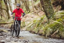 Front view of mountain biker walking with bicycle in stream at forest — Stock Photo