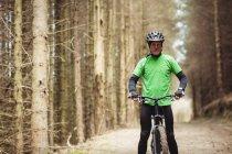 Portrait de motard debout près des arbres dans la forêt — Photo de stock