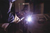 Міделю жіночий зварювальник, працюючи на шматок металу в майстерні — стокове фото