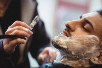 Uomo ottenere la barba rasata con rasoio in negozio di barbiere — Foto stock