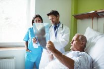 Arzt und Krankenschwester interagieren über Röntgenbericht mit Patient im Krankenhaus — Stockfoto