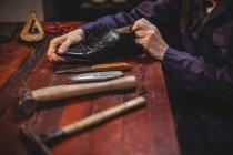 Seção média de sapateiro masculino reparando um sapato na oficina — Fotografia de Stock