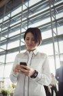 Азиатская пассажирка с мобильного телефона в терминале аэропорта — стоковое фото