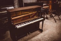Old wooden piano at workshop interior — Stock Photo