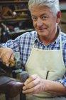 Senior shoemaker hammering on a shoe in workshop — Stock Photo