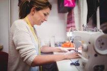 Женский портниха шьет на швейной машинке в студии — стоковое фото