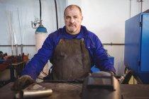 Portrait of welder sitting in workshop — Stock Photo