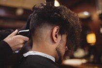 Visão traseira do homem recebendo seu cabelo aparado com aparador na barbearia — Fotografia de Stock