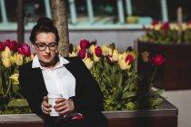 Бизнесмен с одноразовой чашкой кофе против цветов — стоковое фото