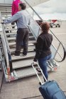 Passengers climbing on the stairs and entering into the airplane at airport — Stock Photo